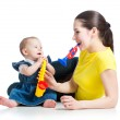 Mother and baby girl having fun with musical toys. Isolated on w — Stock Photo #21851401