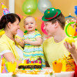 Baby girl celebrating first birthday with parents and clown — Stok fotoğraf