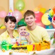Baby girl celebrating first birthday with parents and clown — Stock Photo #22152623