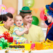 Foto Stock: Baby girl celebrating first birthday with parents and clown