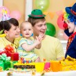 Foto de Stock  : Baby girl celebrating first birthday with parents and clown