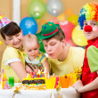Baby girl celebrating first birthday with parents and clown — Stock Photo #22152639
