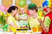 Niña celebrando el primer cumpleaños con padres y payaso — Foto de Stock