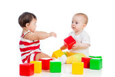 Two babies or kids playing together with color toys — Stock Photo