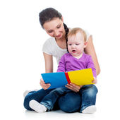 Happy mother reading a book to child girl — Stock Photo