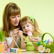 Mother and child girl paint easter eggs over green background — 图库照片
