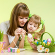 Mother and child girl paint easter eggs over green background — Stock Photo