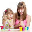 Foto Stock: Kid girl and mother playing colorful clay toy