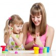 Foto de Stock  : Kid girl and mother playing colorful clay toy