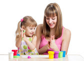 Kid girl and mother playing colorful clay toy — Stock Photo