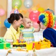 Baby girl celebrating first birthday with parents and clown — Stock Photo #23595719