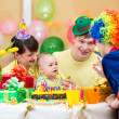 Baby girl celebrating first birthday with parents and clown — 图库照片