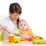 Молодая мать girlisolated ложка кормления своего ребенка на белом — Стоковое фото