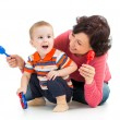 Mother and baby boy having fun with musical toys. Isolated on wh — Photo