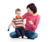 Mother and baby boy having fun with musical toys. Isolated on wh — Stock Photo