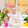 Baby girl celebrating first birthday and eating cake — Stock Photo