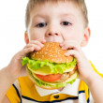 Kid boy eating delicious hamburger — Stock Photo