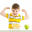 Kid boy eating healthy food and showing strength — Stock Photo #23758519