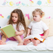 Kids sisters reading a book in bed — Stock Photo #23791343