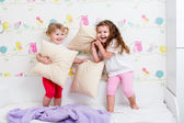 Children sisters playing on the bed indoors — Stock Photo