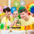 Baby girl celebrating first birthday with parents and clown — Stock Photo