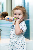 Child girl brushing teeth in bathroom — Stock Photo