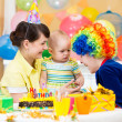 Baby girl celebrating first birthday and clown — Stockfoto