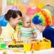 Baby girl celebrating first birthday and clown — Stock Photo