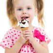 Stock Photo: Joyful child girl eating ice cream in studio isolated