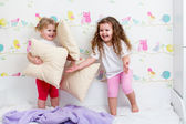 Kids sisters playing on the bed indoors — Stock Photo