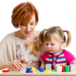 Happy kid girl and mother playing with colorful clay toy — 图库照片