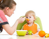 Mother spoon feeding her baby girl — Stock Photo
