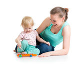 Mother and baby girl having fun with musical toy. Isolated on wh — Stock Photo