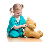 Adorable child with clothes of doctor playing with plush toy — Stock Photo