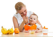 Mother spoon feeding baby boy — Stock Photo