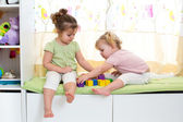 Children sisters play together indoors — Stok fotoğraf