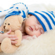 Foto Stock: Newborn baby sleeping on fur bed