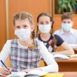 Schoolkids with protection mask against flu virus at lesson — Stock Photo