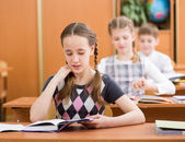 Schoolkids in classroom. Girl reading task aloud at lesson. — Stock Photo