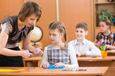 Schoolkids work at labour lesson. Teacher helping pupil. — Stock Photo