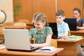 Schoolkids using laptop at lesson — Stock Photo