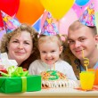 Kid girl with parents blow candles on birthday cake — Stock Photo