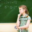 School girl thinking at blackboard — Stock Photo