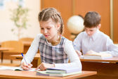 Schoolkids writing to copybook at lesson — Stock Photo