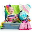 Baby girl sitting in suitcase with things for vacation travel — Stock Photo #25596905