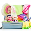 Baby girl sitting in suitcase with things for vacation travel — Stock Photo #25596907