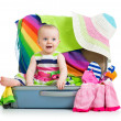 Baby girl sitting in suitcase with  things for vacation travel — 图库照片