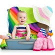 Foto Stock: Baby girl sitting in suitcase with things for vacation travel