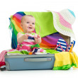 Baby girl sitting in suitcase with things for vacation travel — Stock Photo #25596911