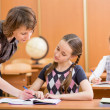 Schoolkids work at lesson. Teacher controling learning process. — Stock Photo